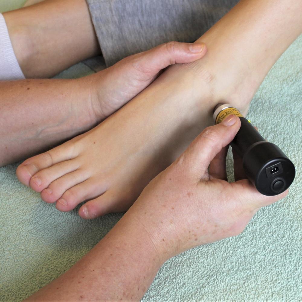 RAB godkendt zoneterapeut Mayanne Damgård ved My-Feet på Adelgade i Skanderborg, giver her en klient laserbehandling for en forstuvet ankel.